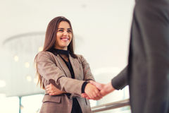 Welcoming business woman giving a handshake. And smiling Stock Image