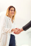 Welcoming business woman giving a handshake. And smiling Stock Images