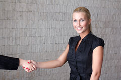 Welcoming business woman giving a handshake and smiling Royalty Free Stock Photo