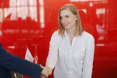 Welcoming business woman giving a handshake and smiling royalty free stock images