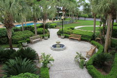 Welcoming courtyard with benches and tropical trees, Beachview Club,Jekyll Island,Georgia,2015 Stock Photos