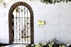 Welcoming Entrance. An iron gate in an archway welcomes you home.  Room on white wall for placards and names Stock Photos