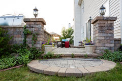 Welcoming entrance to an outdoor patio. In front of a timber house with a decorative circular step from a green lawn between pillars with lamps to a patio with Royalty Free Stock Photography