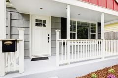 Welcoming front porch boasts pure white front door. Welcoming front porch features pure white front door, handrails and concrete floor. Northwest, USA Royalty Free Stock Photo