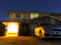 Welcoming home at night with parked car. A lighted and welcoming family home at night by a starry sky. Urban living in Australia. Low-angle shot Royalty Free Stock Photography