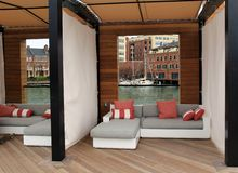 Gorgeous sitting area, tucked into outside corner of pool area, Sagamore Pendry Hotel, Baltimore, Maryland, 2017. Welcoming image of comfy couches and pillows stock photo
