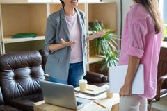 Welcoming new subordinate. One of businesswomen explaining principles of work to the other one Stock Photography
