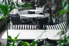 A welcoming outdoor marble tables and chairs with cozy black and white pillows surrounded by  bright green plants on terrace in. A welcoming outdoor marble stock images