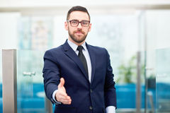 Welcoming partner. Successful broker giving hand for handshake Stock Images