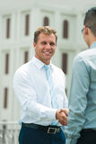 Welcoming partner. Vertical image of a smiling business guy giving a welcoming handshake to his partner Royalty Free Stock Images