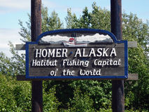A welcoming sign at homer,alaska. A wooden sign announcing the arrival at the halibut fishing capital of the world stock image