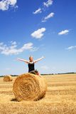 Welcoming the summer sun. Woman enjoying the summer sun sitting on a hay bale under a bright blue sky stock photography