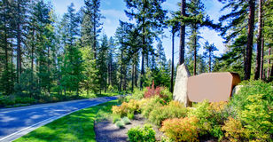 Welcoming Suncadia sign along the driveway. Driveway through the forest. Desert like flower bed with stones. Welcoming suncadia sign stock photos