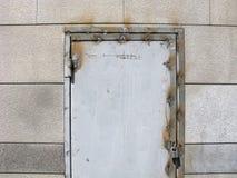 Weld seams on metal door frame and door hinge, padlock on door. Arc welding on the old metal door. Weld seams on metal door frame and door hinge. Padlock on the Stock Photography