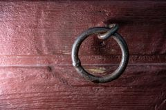 Welded metal link in red wooden wall. Captured with flash to create more contrast to the picture stock photography