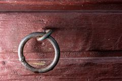 Welded metal link in red wooden wall. Captured with flash to create more contrast to the picture royalty free stock photography