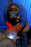 Welder. Man in a workshop busy welding a implement stock photography