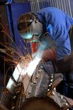 Welder. Man in a workshop busy welding a implement stock images
