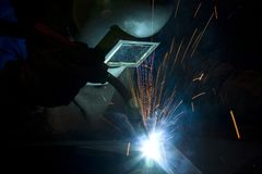 Welder. Industrial worker with welding torch and protective mask Stock Photo
