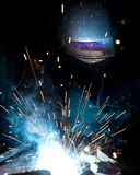 Welder in action with bright sparks. Royalty Free Stock Images