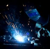 Welder in action with bright sparks. Royalty Free Stock Photo