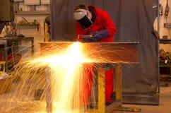 Welder bends to cut metal beam. Stock Image