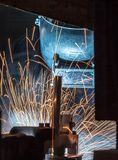 Worker with protective mask welding metal. Welder and bright sparks. Construction and manufacturing Royalty Free Stock Photos