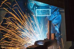 Worker with protective mask welding metal. Welder and bright sparks. Construction and manufacturing Stock Photography