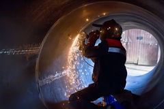 Welder carries out mechanical cleaning of root surfaces of weld Stock Photos