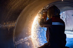 Welder carries out mechanical cleaning of root surfaces of weld Stock Images