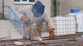 Welder at construction site is welding pipe with electrode in helmet. stock video