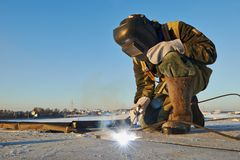 Welder at construction site. Welder working with electrode at arc welding in construction site winter outdoors Royalty Free Stock Photos