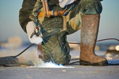 Welder at construction site. Welder working with electrode at arc welding in construction site winter outdoors Stock Images