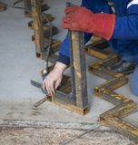 Welder is controlling angle of iron construction. Image of welder is controlling angle of iron construction Stock Photos