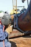 Welder in coveralls makes a weld on a pipe of large diameter Stock Images