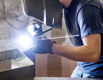Welder doing welding in a metal workshop. Welder or metalworker doing welding in an industrial metal workshop wearing a visor and gloves to protect his eyes and Royalty Free Stock Photography