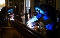 Welder in factory. A metal welder at work wearing a mask with sparks flying Royalty Free Stock Photo