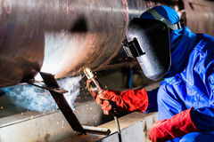 Welder in factory welding metal pipes. Welder working in industrial workshop Royalty Free Stock Image