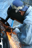 Welder with grinder. Welder with hand grinder, sparks flying royalty free stock image