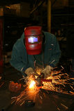 Welder with grinder. Welder with helmet grinding metal, making sparks Stock Images