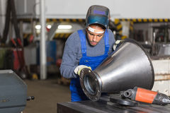 Welder inspecting  metal piece for quality control Stock Image
