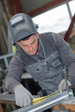 Welder man measuring part in workshop Stock Photography