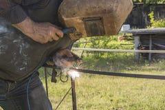 Welder. Man in protective mask welds metal design elements Stock Photography