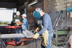 Welder or metalworker in workshop. Welder or metalworker with protective clothing in workshop Royalty Free Stock Image