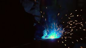 Welder på arbete i metallbransch Mannen arbetar på byggnad Welderen fungerar i en hangar Gnistor från svetsning arkivfilmer