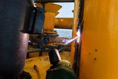 Welder perform welding to the metal plate at roof floor of manuf. Acturing factory by using steel welding electrode in offshore oil and gas industrial operation Stock Image