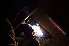 Welder perform welding. Welder perform welding to the metal plate by using steel welding electrode in offshore oil and gas industrial operation Royalty Free Stock Photos