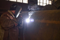 Welder performs welding large diameter pipe Stock Photo