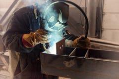 Welder performs welding work of metal structures royalty free stock photo