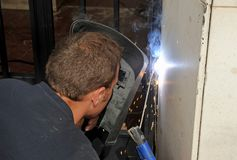 A welder placing a new iron door at the entrance of the apartment building with electric arc welding. Renovation works of the main door of an apartment building Royalty Free Stock Photography